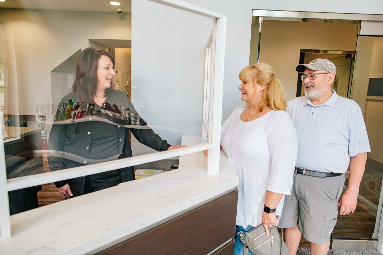Dental Patients Smiling at Front Desk Receptionist Behind Plexiglass